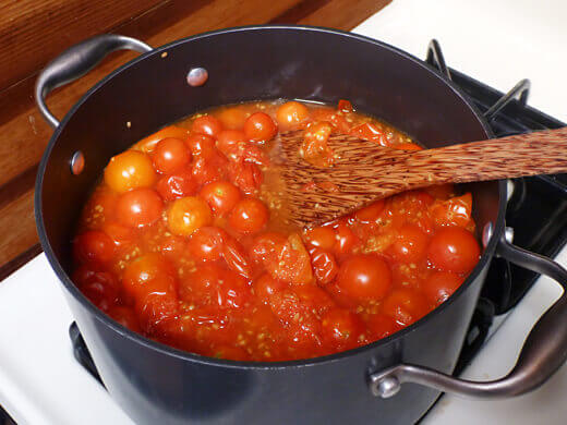 Stir tomatoes as they simmer in their own juices