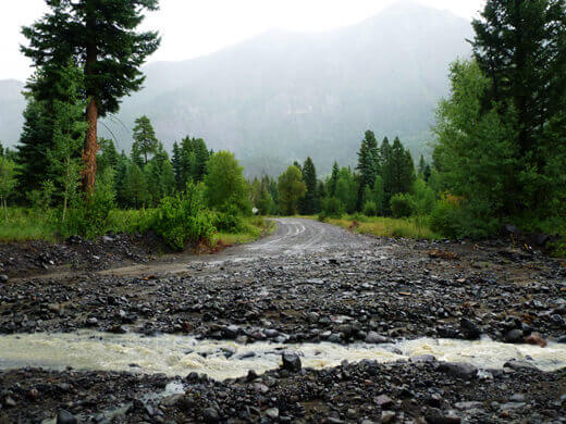 Road washed out by a rocky creek