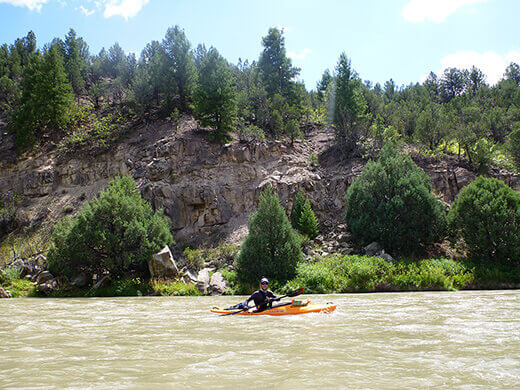 Paddling past desert brush and rocky slopes on the Rio Chama