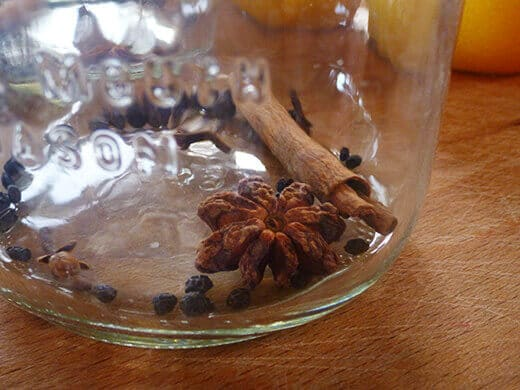 Add cinnamon stick, cloves, star anise, and black peppercorns to a jar