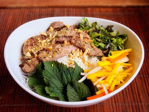 Vietnamese daikon and carrot pickles in a bowl of vermicelli and grilled pork