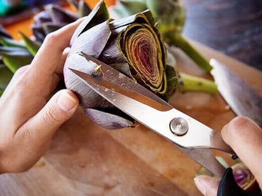 Snip the tips of artichoke leaves