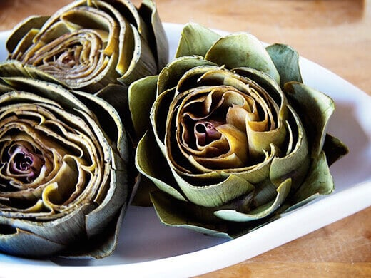 Pry artichoke leaves apart to prepare for stuffing
