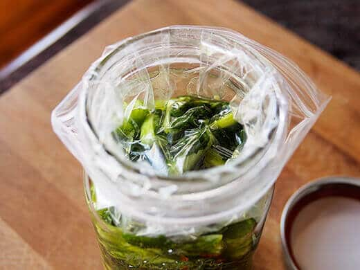Line the jar with a weighted baggie to keep the veggies submerged
