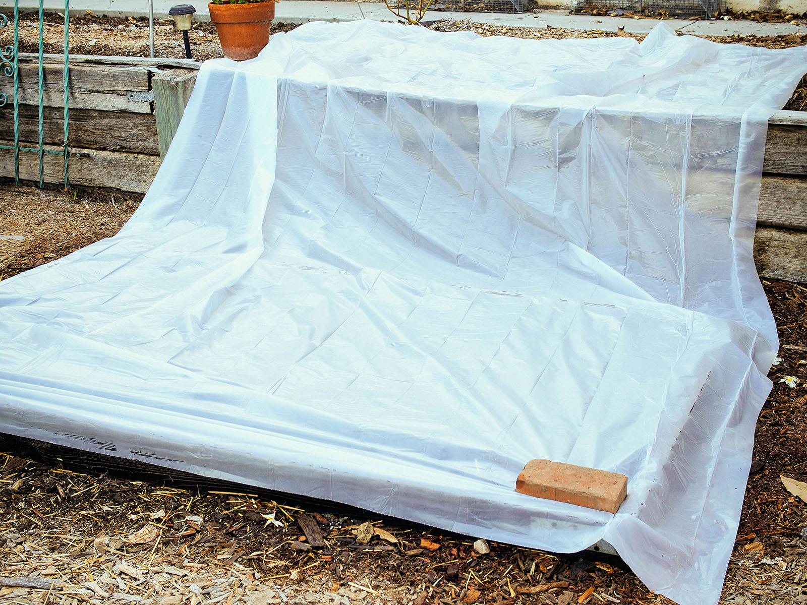 Lay the plastic over the bed