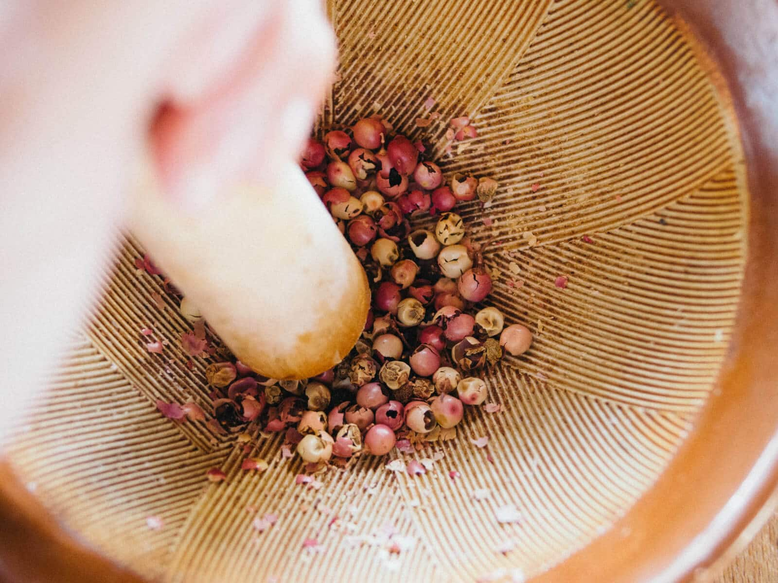 Crushing pink peppercorns with a mortar and pestle