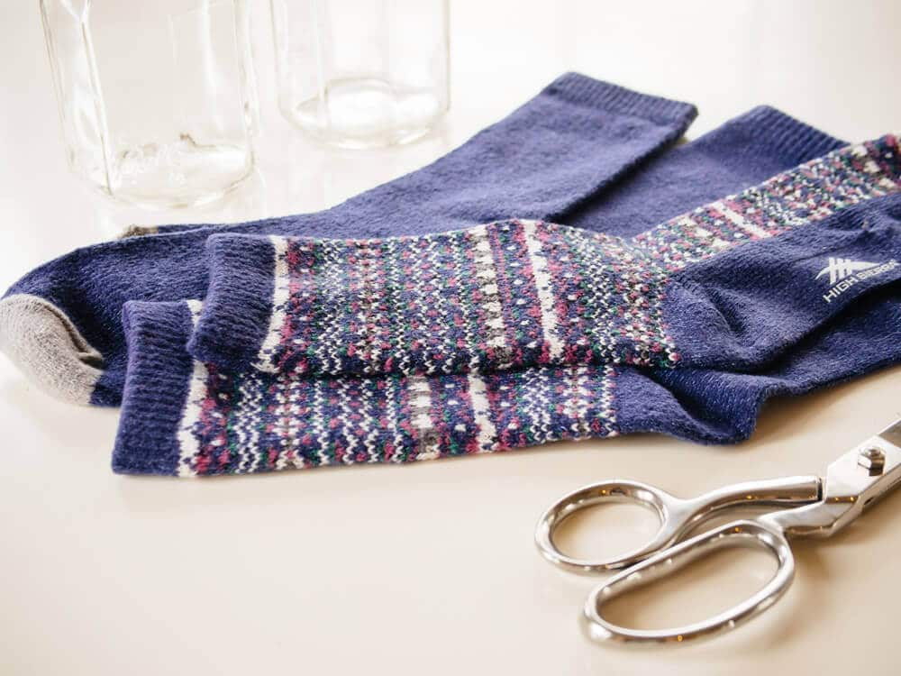 Gather socks, scissors, and needle and thread