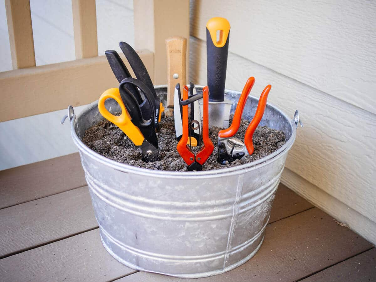 Store gardening tools in a bucket filled with sand and oil to prevent rust and keep blades sharp