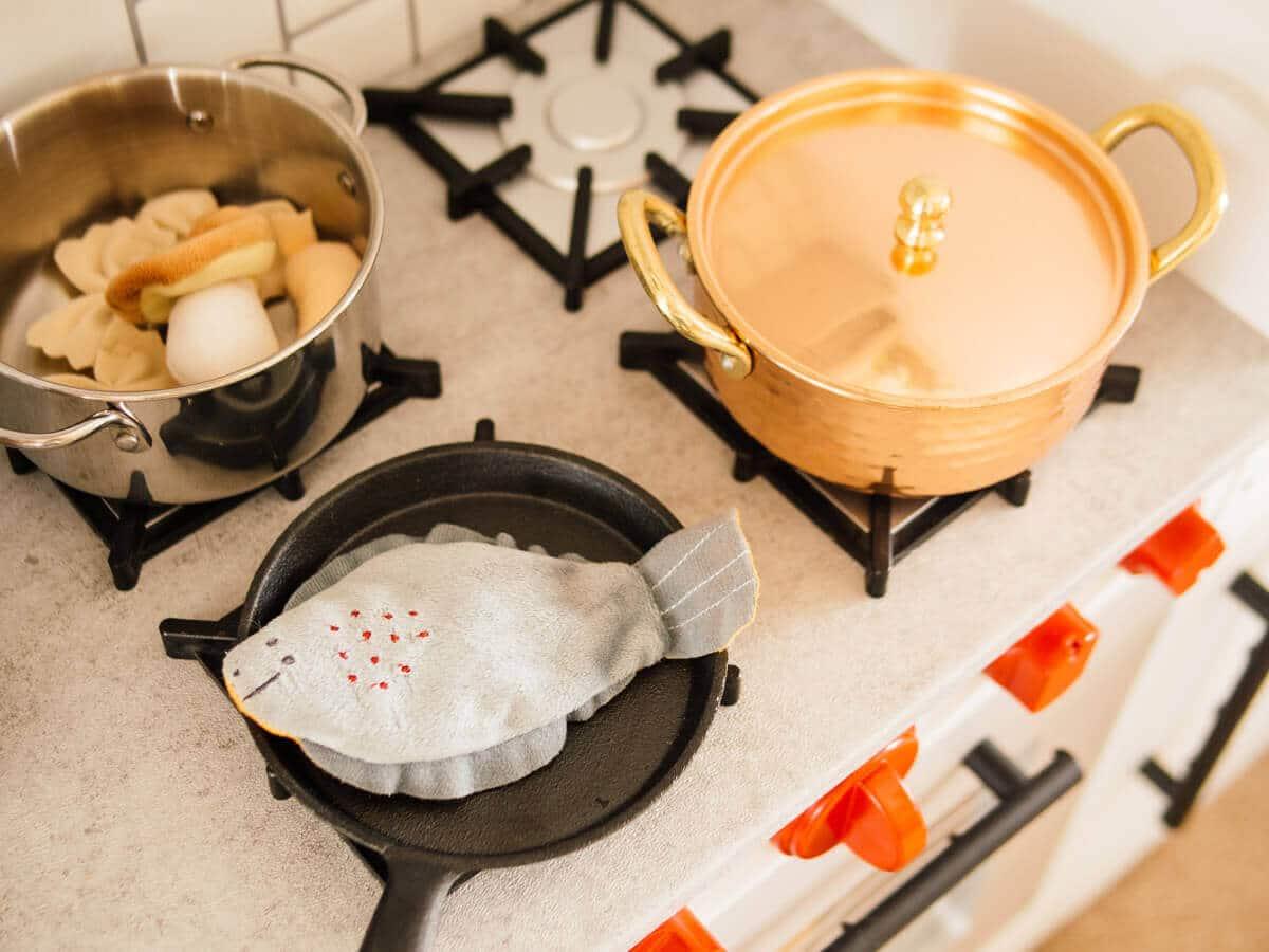 """Concrete"" counters, mini cast iron pan, and mini copper pot in a play kitchen"