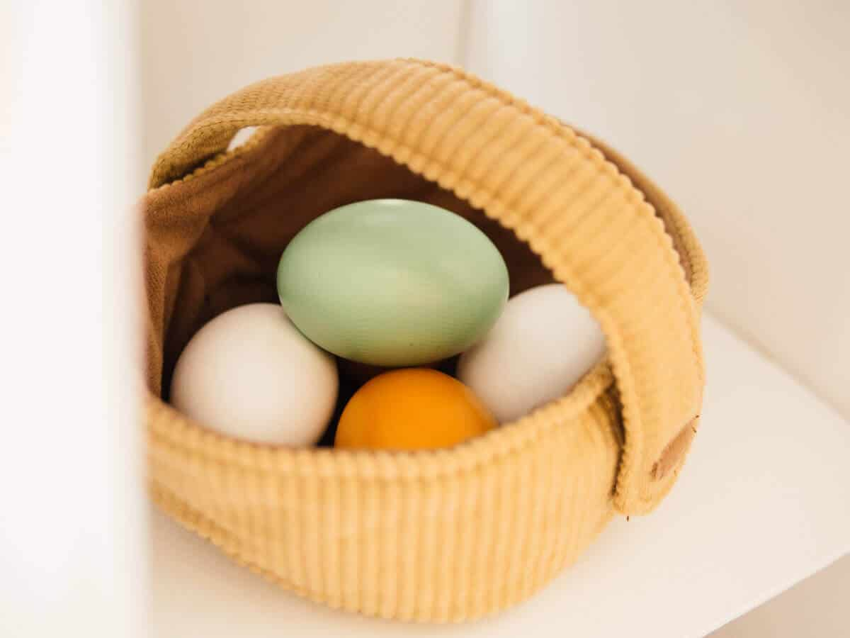 Multi-colored wooden eggs in basket