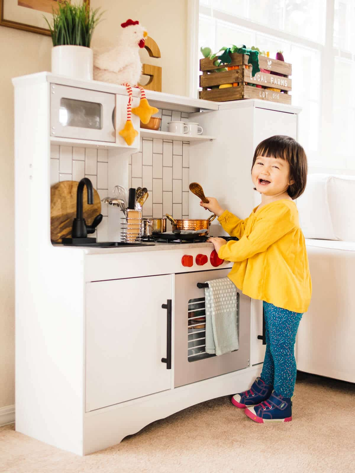 Cooking in her remodeled KidKraft play kitchen