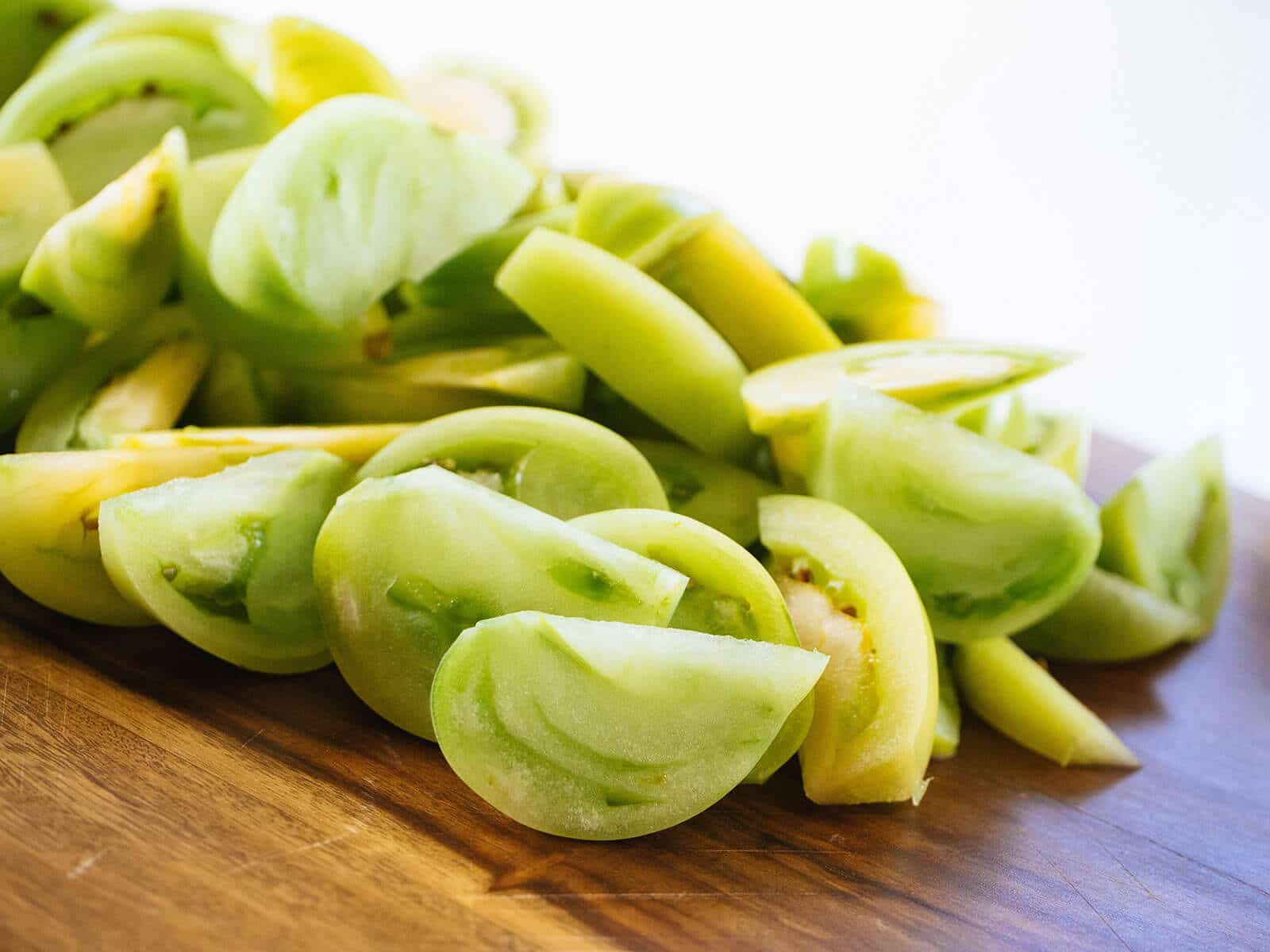 Sliced green tomatoes on a cutting board