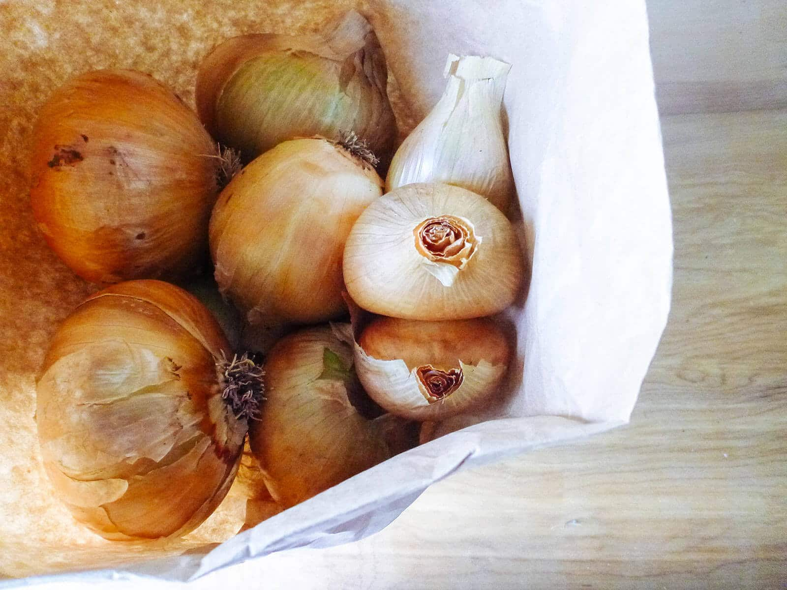 Yellow onions stored in brown paper bag