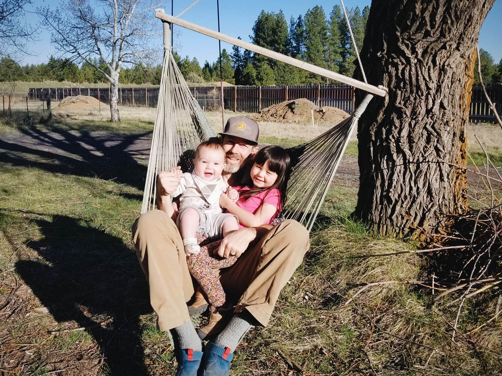 Dad and daughters on a tree swing