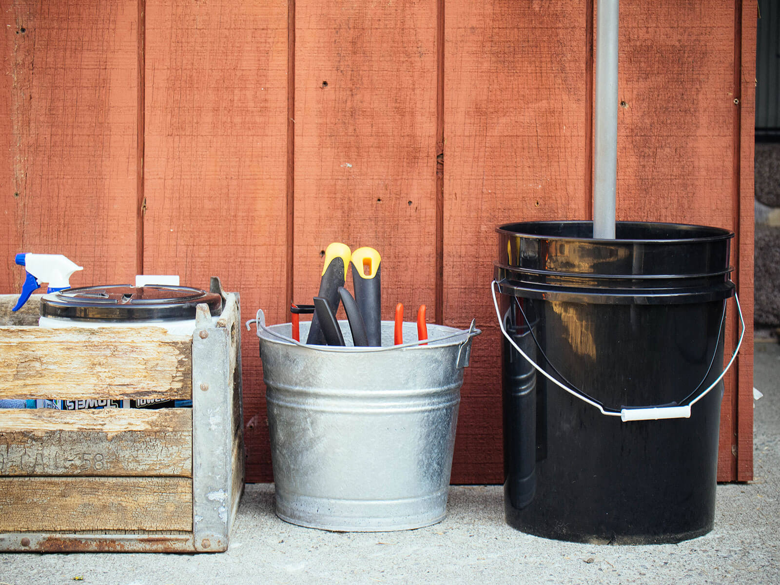 Crate of cleaning supplies and two buckets filled with tools, set against a shed wall