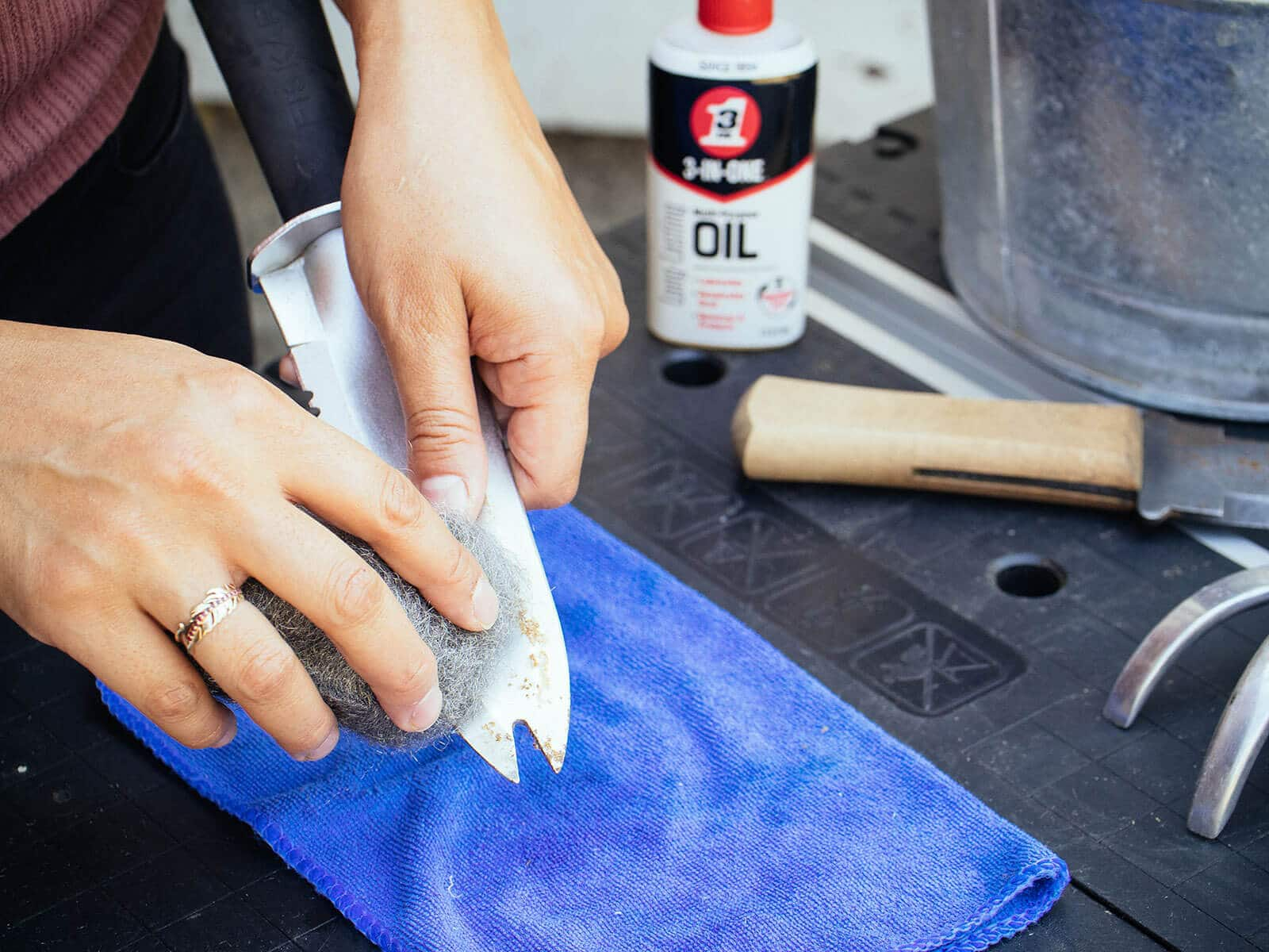 Hand scrubbing rust off a hori hori knife with steel wool