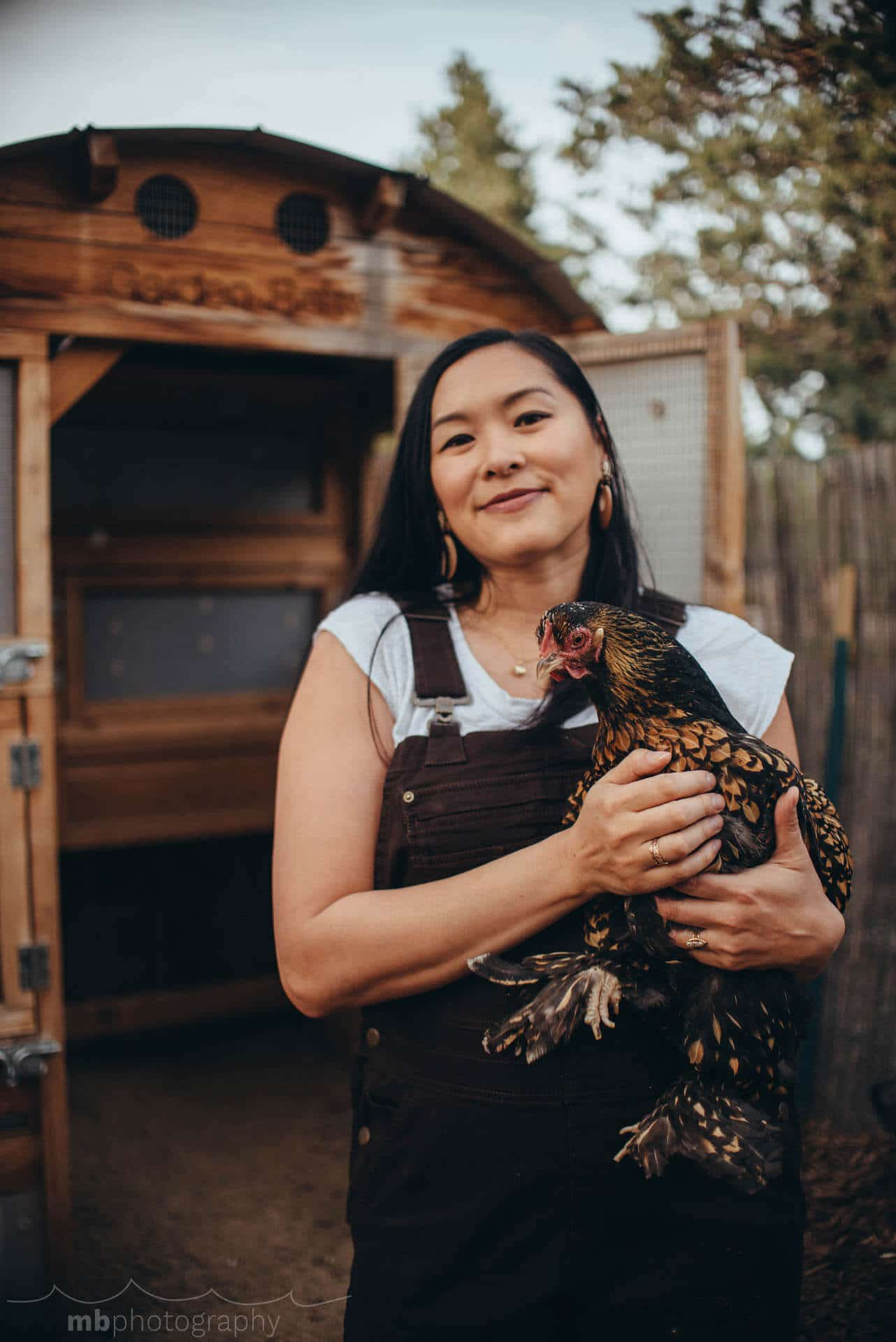 Garden Betty holding a Golden Laced Cochin chicken in front of the coop