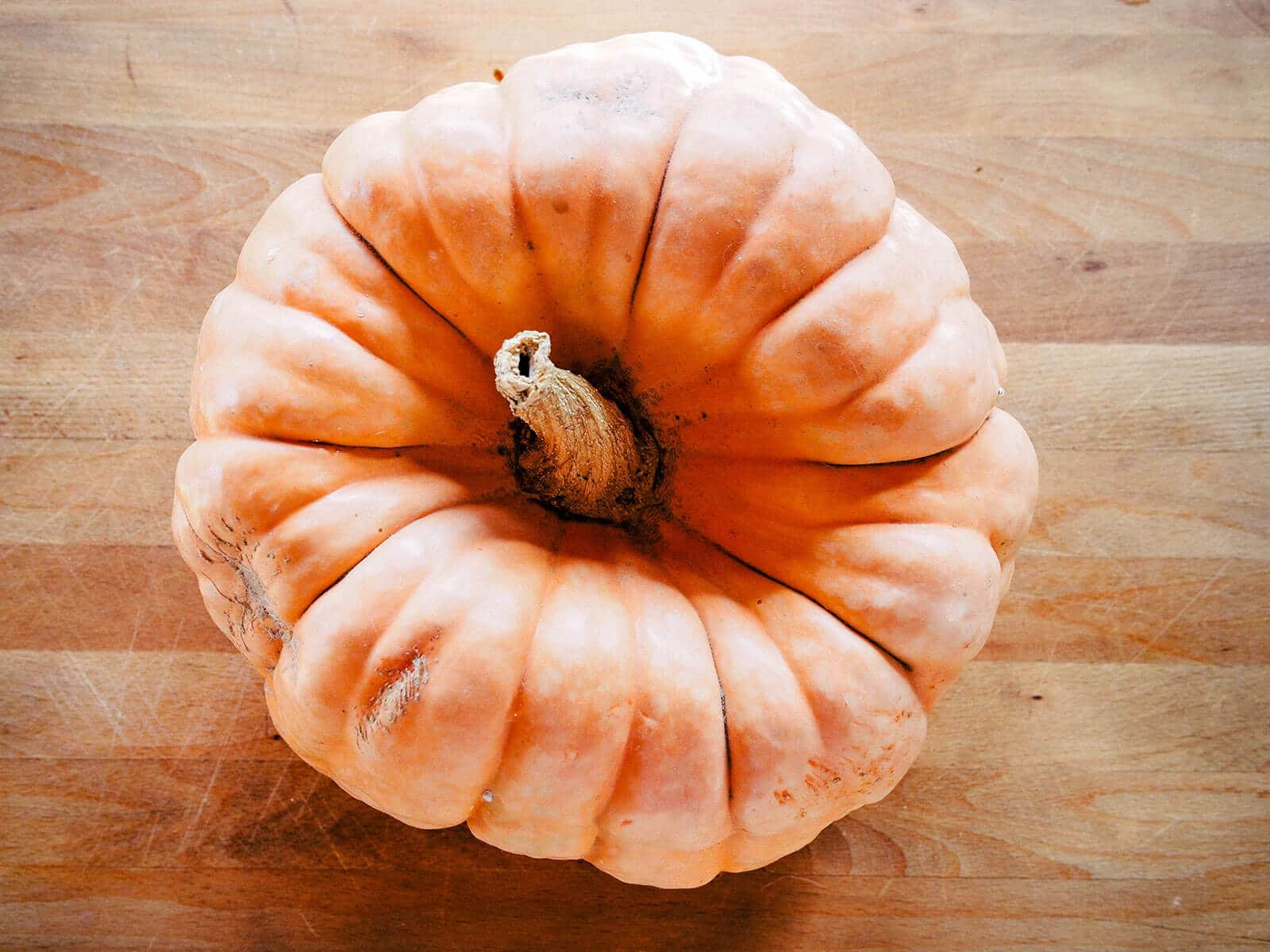 Overhead view of a ribbed pumpkin on a butcher block counter