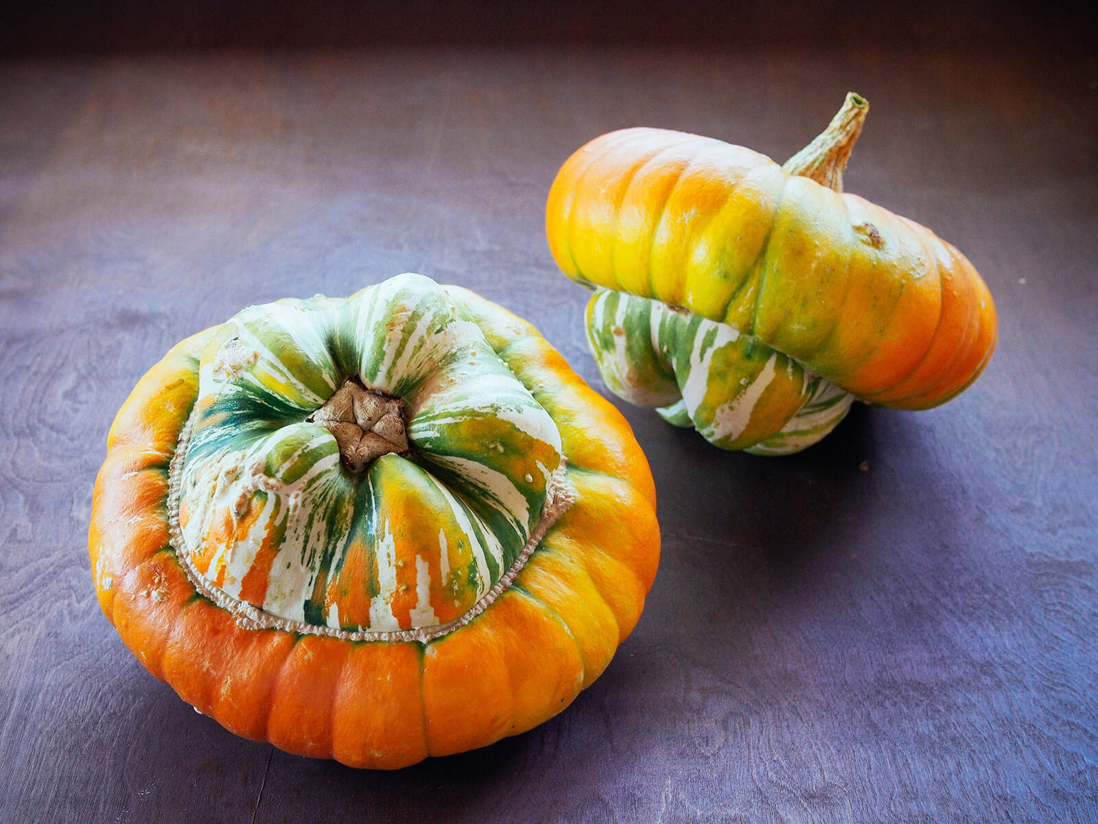 Two turban squash sitting on a wooden table