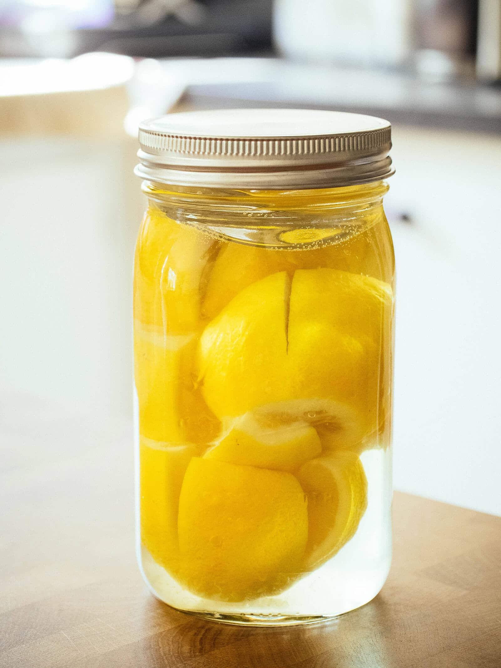 Jar full of lemons being preserved in brine